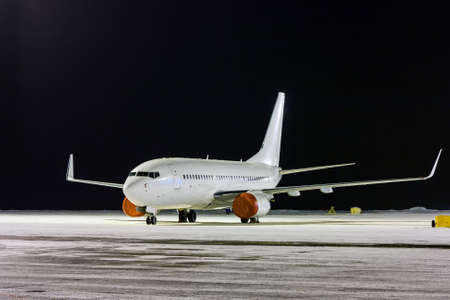 White passenger airplane on the night airport apron at winter 版權商用圖片 - 156249761