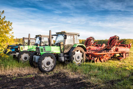 Modern wheeled agricultural tractors with harvesting equipment on an field