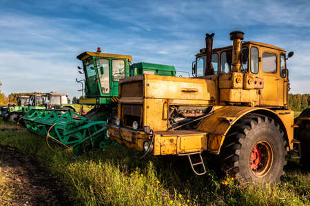 Wheeled tractors and combine harvester standing in a row on an agricultural field 版權商用圖片 - 155823363