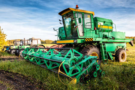 The modern combine harvester and wheeled agricultural tractors on field