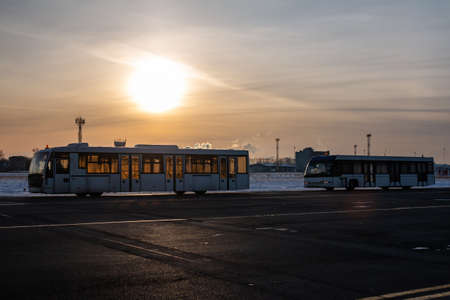 Two empty airport shuttle buses in a cold winter evening