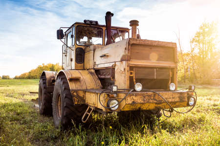 Heavy duty wheeled tractor on an agricultural field in the rays of the autumn sun 版權商用圖片