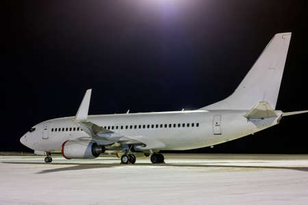 White passenger aircraft on the night airport apron at winter
