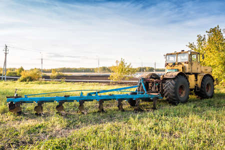 Wheeled agricultural tractor with harvesting equipment on an field Фото со стока