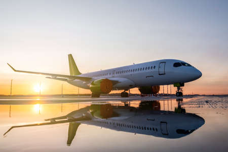 Modern passenger airplane on the apron of the airport against the backdrop of a picturesque sunset with reflection in a puddle