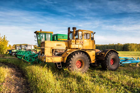 Wheeled tractors and combine harvester standing in a row on an agricultural field
