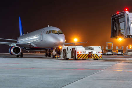 Tow tractor pushes passenger aircraft from boarding bridge at night airport apron Фото со стока
