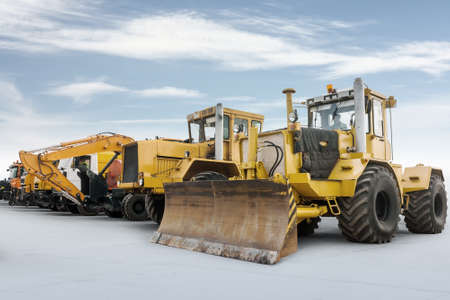 Two heavy wheeled tractor one excavator and other construction machinery isolated on bright background