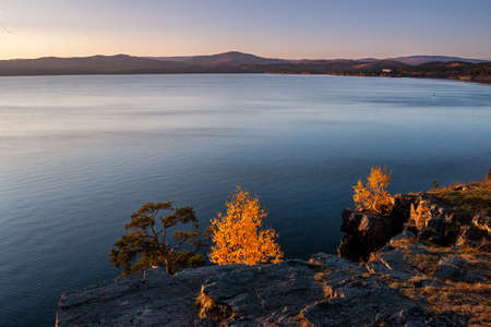 Beautiful lake and rocky shore on a clear sunny day of golden autumn Фото со стока