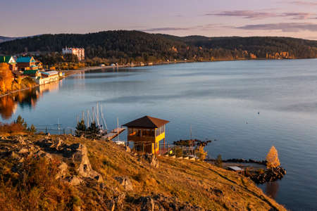 View of the bay of the picturesque lake from the rocky shore in the evening light in golden autumn