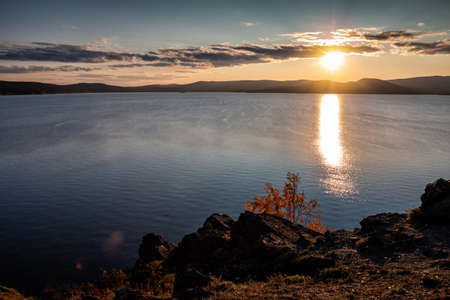 Beautiful lake and rocky shore in the rays of evening sun of golden autumn