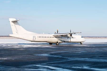 White passenger turboprop aircraft on the airport apron in cold winter weather Фото со стока