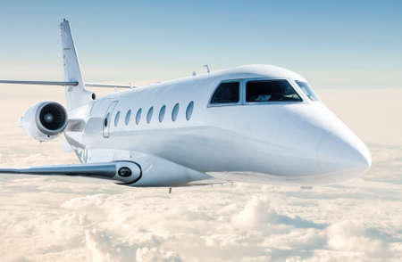 White modern luxury business jet flies in the air above the clouds. Close-up view corporate airplane Фото со стока
