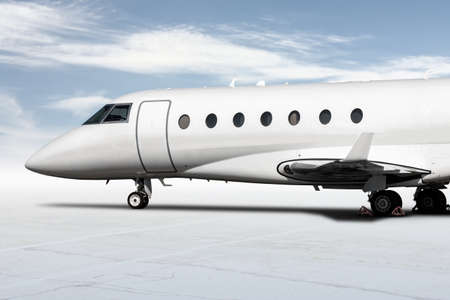 Close-up of the modern white corporate business jet isolated on bright background with sky Фото со стока