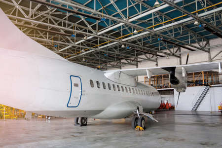 White passenger turboprop aircraft under maintenance in the hangar. Repair of airplane and checking mechanical systems for flight operations