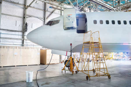 Front view of the white passenger aircraft under maintenance in a hangar. Checking mechanical systems for flight operations. The airplane has an open front door