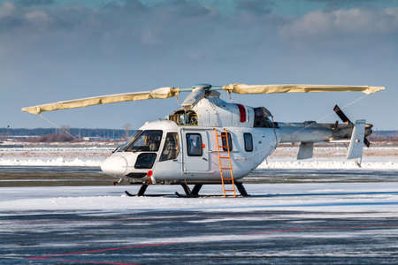 White helicopter with an open engine on the apron of a winter airport Фото со стока
