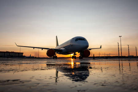 Modern passenger airliner on the airport apron against the backdrop of a scenic sunset with reflection in a puddle Фото со стока