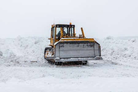 Yellow bulldozer removes snowdrifts in a severe snowstorm at winter Фото со стока