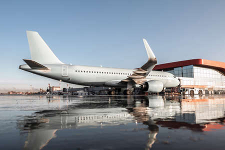 Passenger aircraft parked to a jet bridge with reflection in a puddle