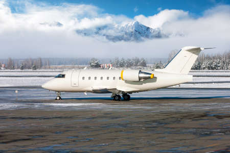 White luxury business jet on the winter airport apron on the background of high scenic mountains on a clear sunny day