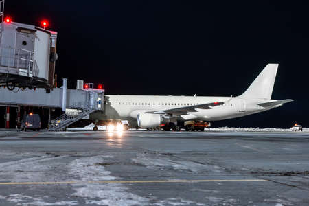Modern passenger jet plane at the air bridge on night airport apron