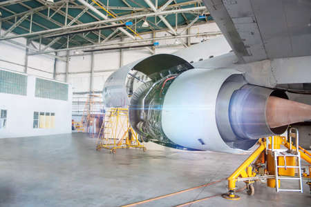 Close-up repair of aircraft engine on the wing. White passenger airplane under maintenance in the hangar. Checking mechanical systems for flight operations