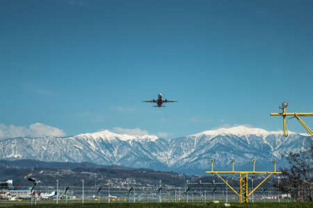 Takeoff of a passenger airplane against the backdrop of high scenic mountains Фото со стока