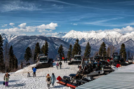 Sochi, Russia - March 31, 2021: Krasnaya Polyana Resort on a clear sunny day. View of the high mountain peaks covered with snow. Snow groomers parking at the top Редакционное