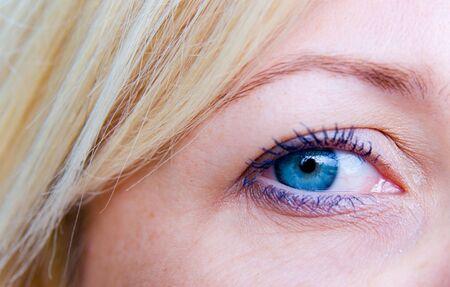 dilate: Beautiful blond woman`s open blue eye  Stock Photo