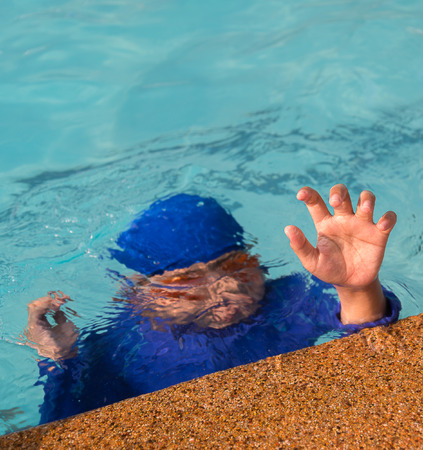 cramps: A boy drowning in the pool, swimming cramps Stock Photo