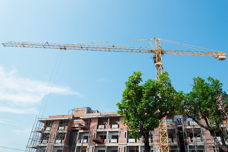 overrun: Green trees stand in front of Crane and building construction site against blue sky.