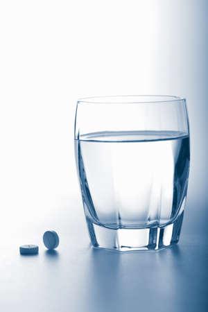 aspirin: aspirin pills and glass of water toned blue