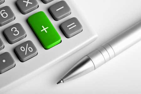 profiting: calcolatrice e penna. oltre a pulsante colorato di verde Archivio Fotografico