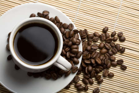 trivet: white cup of coffee and coffee beans over bamboo background Stock Photo
