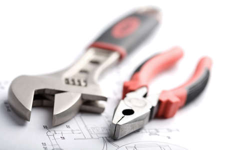 wrench and pliers over technical drawing isolated photo