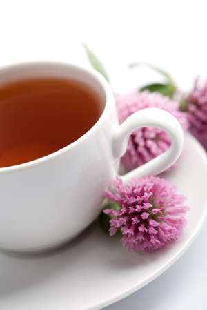 white cup of herbal tea and clover flowers isolated photo