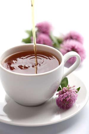 thé couler dans la tasse blanche isolé