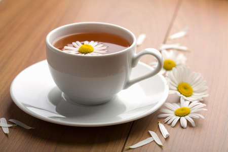 white cup of herbal tea and camomile flowers photo