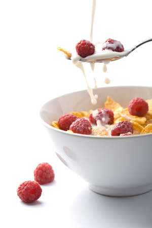 cereal bowl: milk pouring onto muesli with raspberry isolated