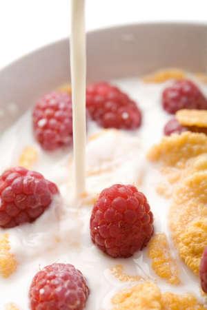 milk pouring onto muesli with raspberry isolated Stock Photo - 4548174
