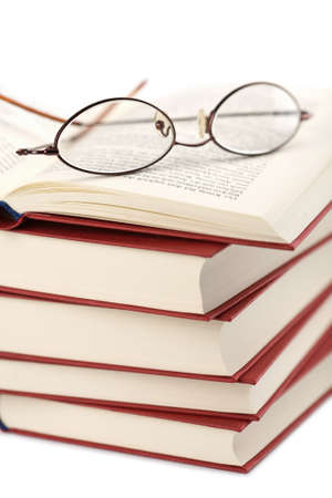bibliomania: pile of books with glasses isolated Stock Photo