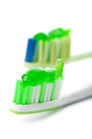 two toothbrushes with green toothpaste isolated photo