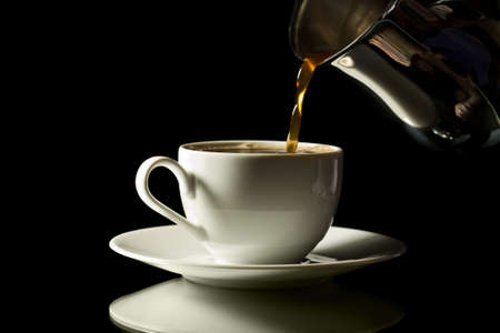 selected: coffee pouring into white cup isolated over black background Stock Photo