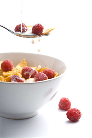 milk pouring onto muesli with raspberry isolated  photo