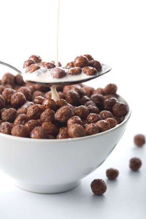 milk pouring into bowl with chocolate balls isolated Stock Photo - 4649902