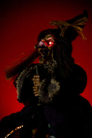 bedlam: witch puppet with red glowing eyes over red background Stock Photo