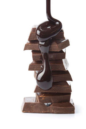 chocolate block: chocolate syrup being poured onto chocolate pieces isolated