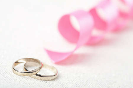 Golden wedding rings and pink ribbon Stock Photo
