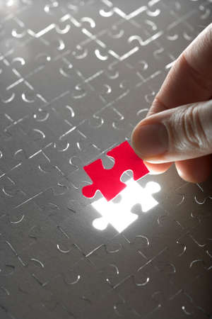 jigsaw: hand holding red puzzle piece